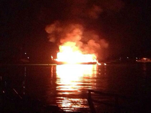 Burning diving vessel towed off Chalong Harbor to sink