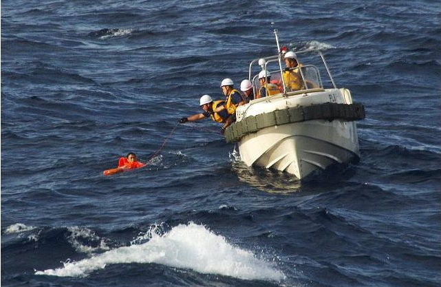 Japan Coast Guard personnel pull Chinese crew from the ocean after their fishing boat collided with a cargo ship and sank near the Senkaku Islands - Aug11,2016