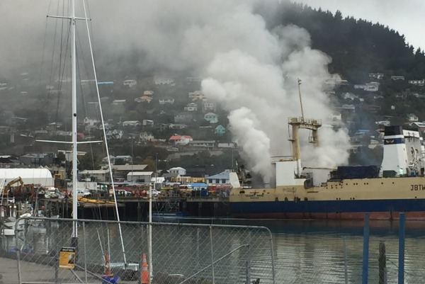 Smoke billowing from the fishing vessel on fire at Lyttelton Port of Christchurch, New Zealand on Apr 18, 2016