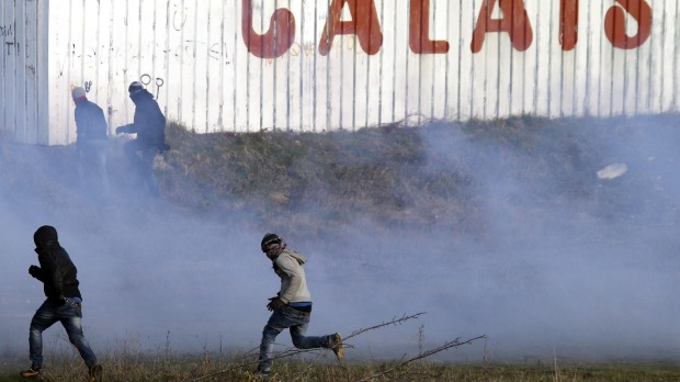 Migrants run away from tear gas thrown by police forces near the Channel Tunnel in Calais, ahead of attempts to raze the camp on Thursday