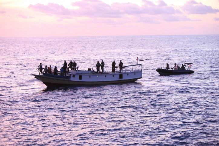 A vessel of interest is boarded at dusk via Rigid Hull Inflatable Boats (RHIB) from HMAS Wollongong